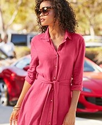 model wearing a pink collared long-sleeve linen dress with a tie-waist and sunglasses.