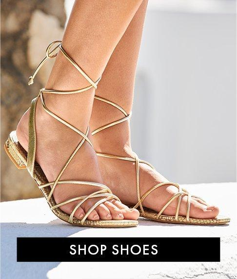 model wearing gold lace-up sandals.