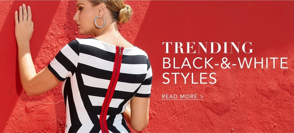 model facing a red wall wearing a black and white striped dress with a red zipper along the back.