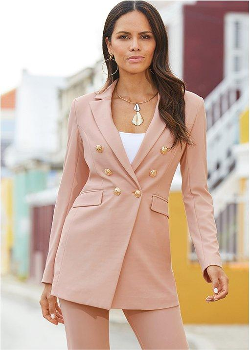 model wearing a petal pink travel blazer, petal pink travel pants, a white tank top, and metal necklace.