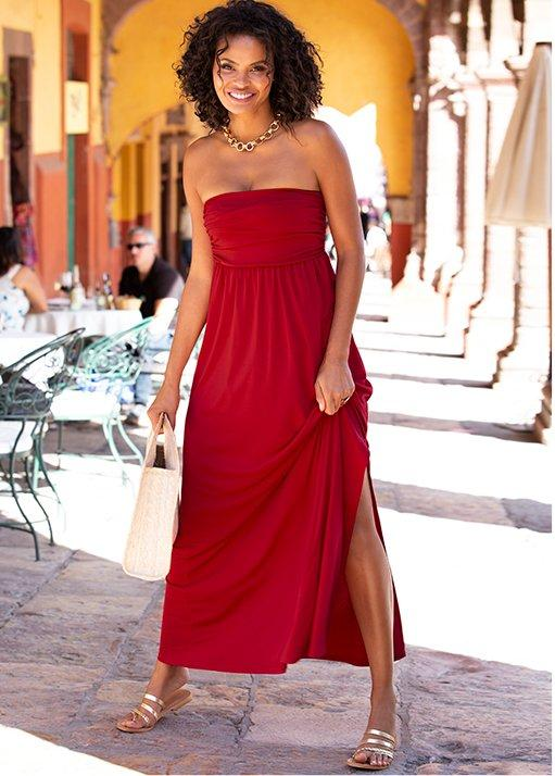 model wearing a red tube top dress with a gold chain necklace and gold strappy sandals.