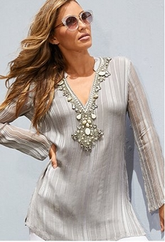 model wearing silver tunic with jewel embellishments.